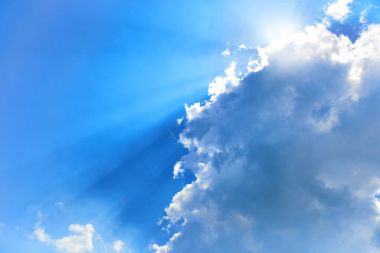 Beautiful blue sky with sunbeams and clouds. Sun rays showing shades of blue.