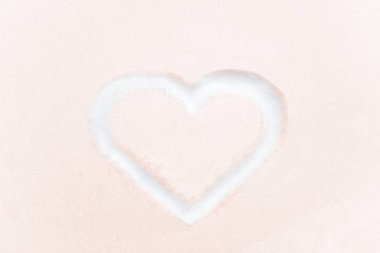 Heart shape drawing on white snow for St. Valentine Day