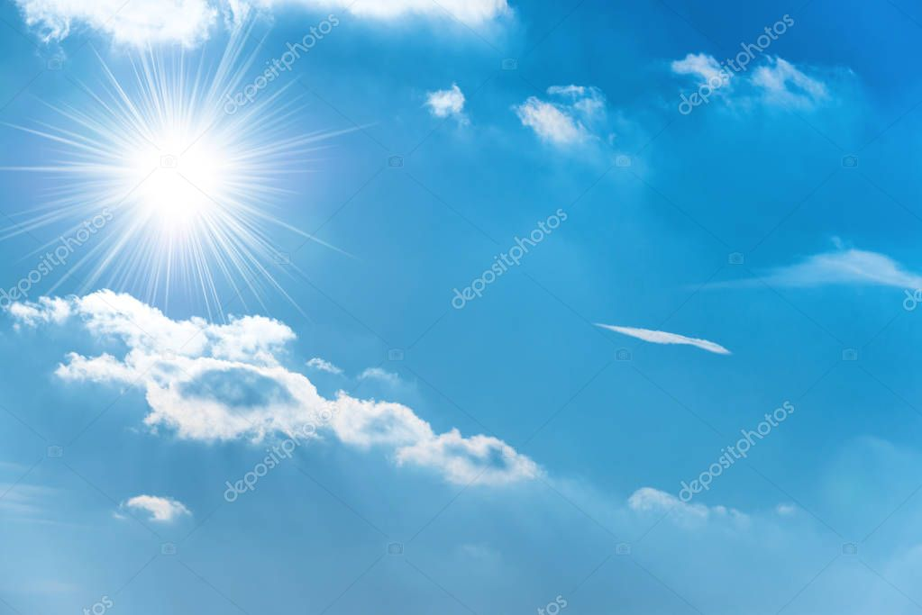 Shining sun on blue sky with torn clouds