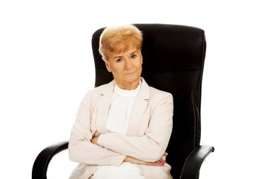 Angry elderly business woman sitting on armchair with folded arms