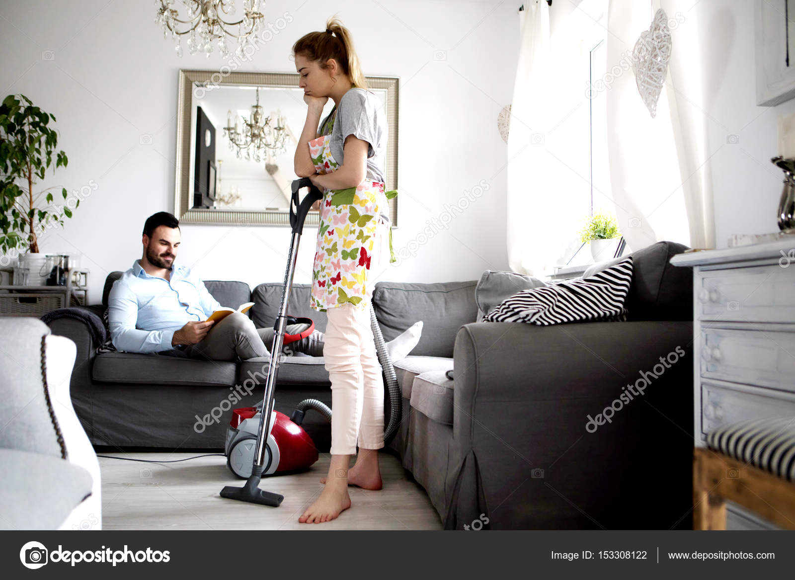 Woman Doing Chores Using Vacuum Cleaner On Carpet And Lazy Man On