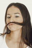 donna teenager mettendo capelli come baffi