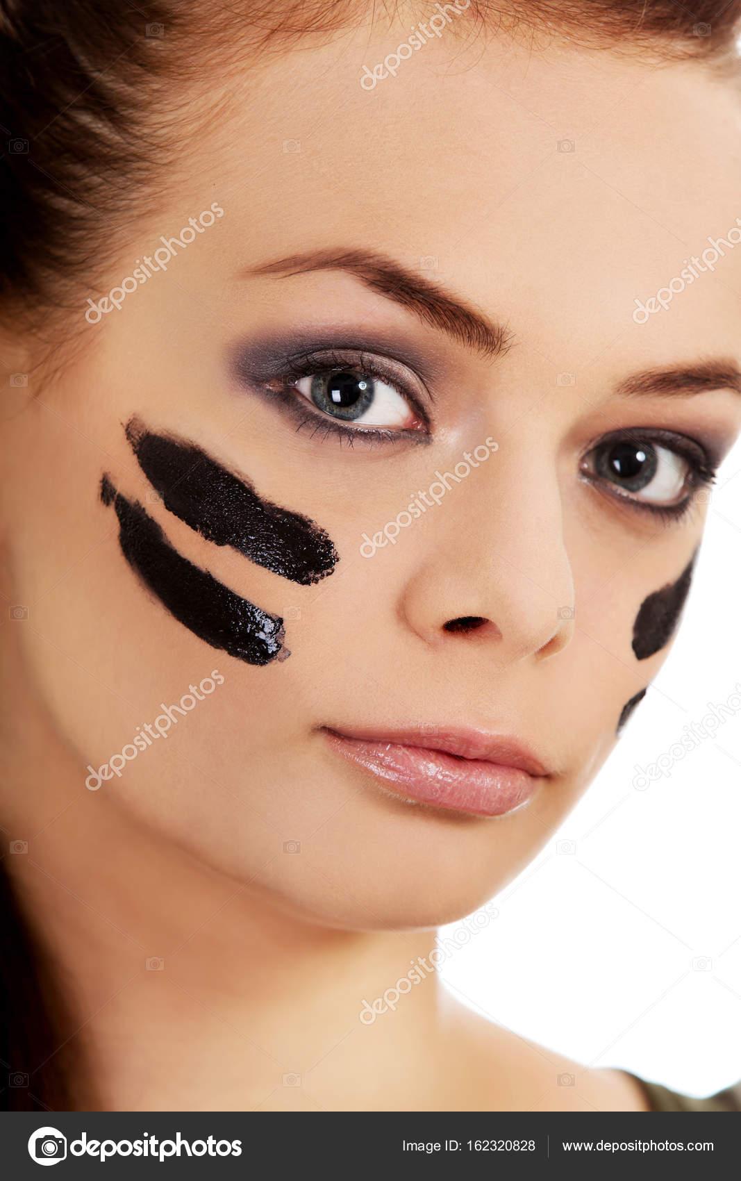 Giovani donne militare con vernice di guerra sul viso\u2013 immagine stock
