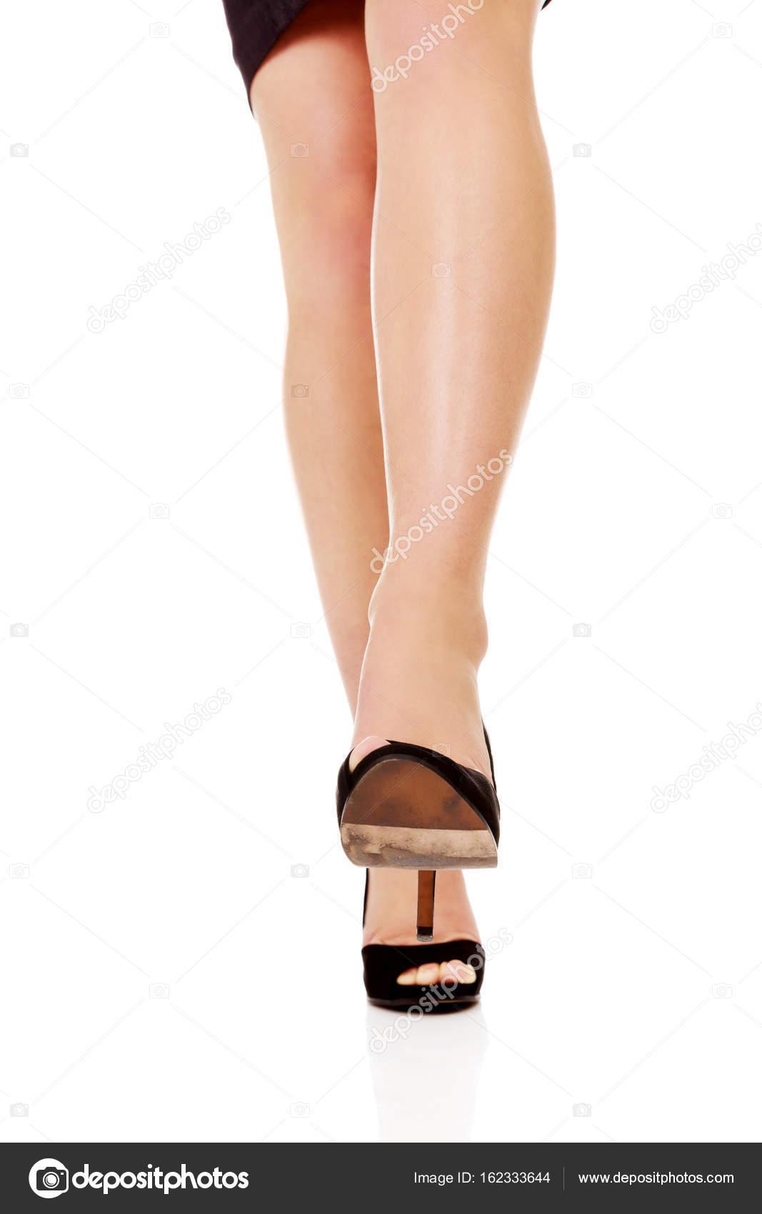 914dc2edec Γυναικείο πόδι σε ψηλά τακούνια που προσπαθεί να ποδοπατήσουν κάτι– εικόνα  αρχείου