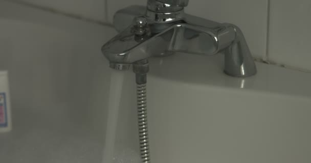 Ezüst csaptelep van kapcsolva, a töltés kád vízzel.