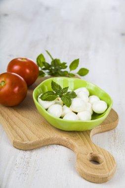 Mozzarella in a green plate on a wooden table. Mozzarella balls