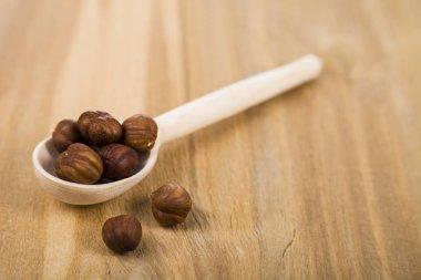 Hazelnut in a spoon on a wooden table