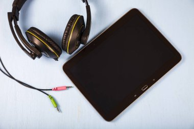 Tablet and headphones on a blue wooden table