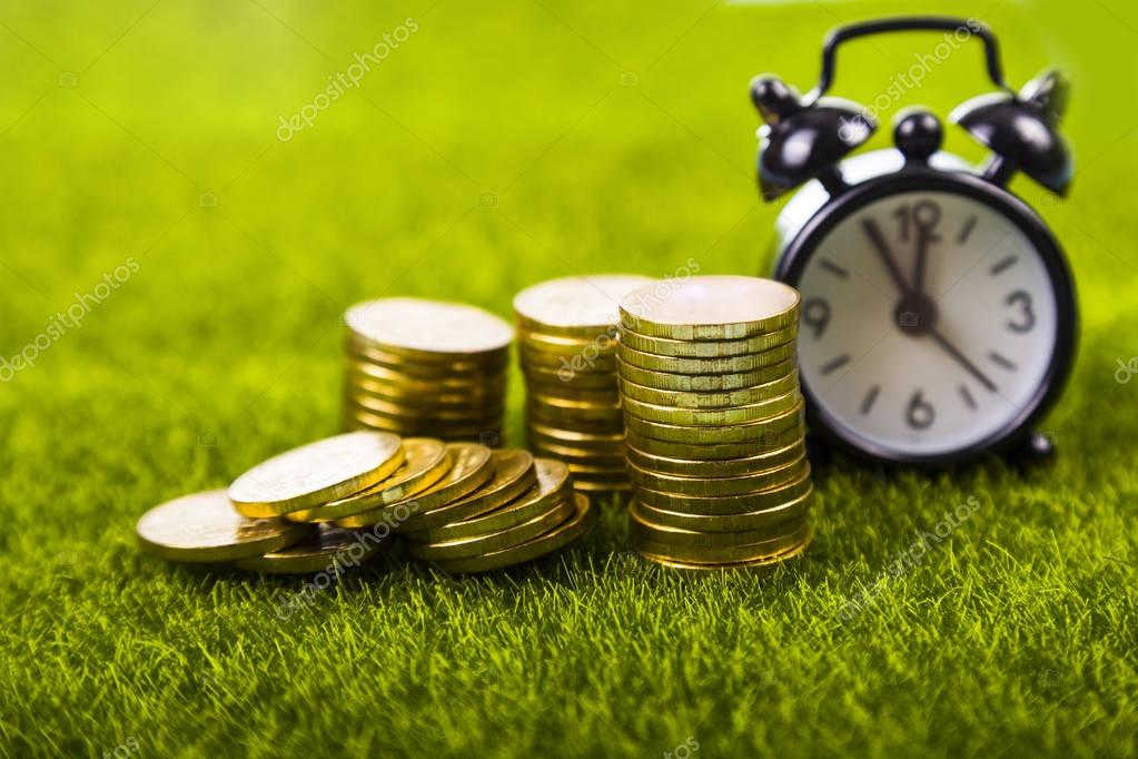 Alarm clock and coins on  grass.