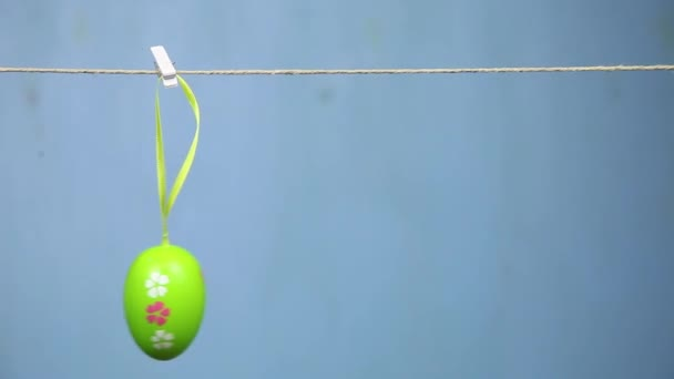 woman hangs Easter eggs on a rope. Blue background.