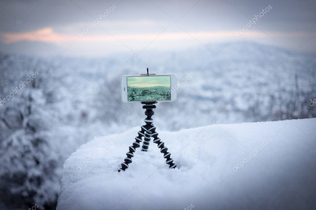 Taking photo of city during winter snow using tripod and smartphone