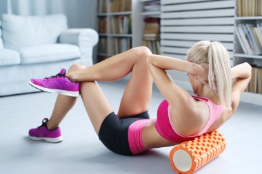 Woman exercises with foam roller