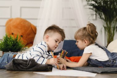 Two kids drawing with pencils