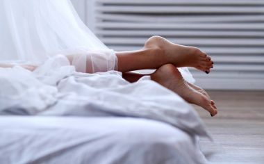 feet of young woman lying in bed, closeup