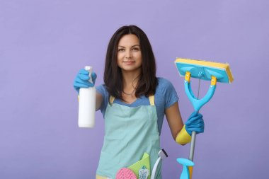 smiling attractive young housemaid showing mop and cleaning spray bottle on purple background
