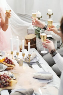 people clanging glasses of champagne together at wedding party, closeup