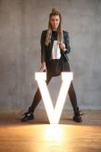 Fotografia acconciatura e moda, giovane donna attraente con i dreadlocks, lettera decorazione V