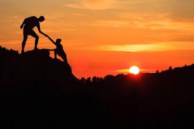 Teamwork couple helping hand trust in inspiring mountains