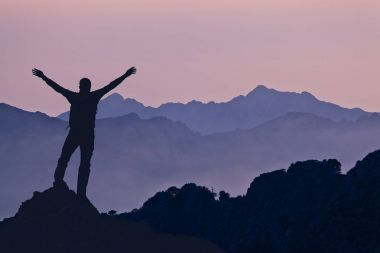 Successful hiking or climbing silhouette in mountains