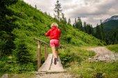 Mladá žena běží na mostě v horách v letním dni