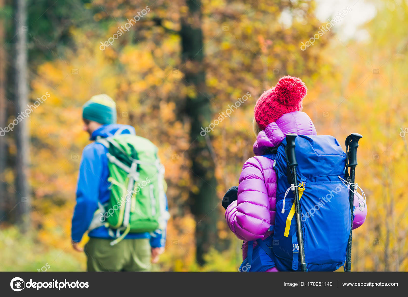 9be7adbbab435e Happy couple hikers trekking in beautiful yellow autumn forest and mountains.  Young people man and woman walking on trek trail with backpacks, healthy ...