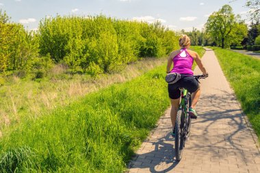Woman cycling a mountain bike in city park, summer day