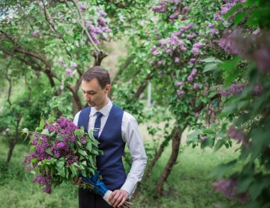 Handsome groom  with  bouquet of lilacs
