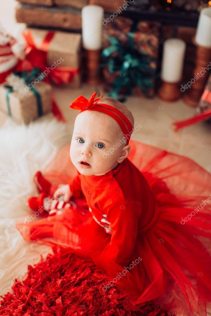 girl in red dress with Christmas tree decoration