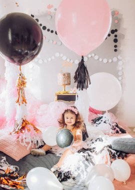 baby girl with  balloons in room