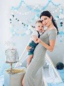 Fotografie Mladá matka a její rozkošný chlapeček s dortem doma u stanu