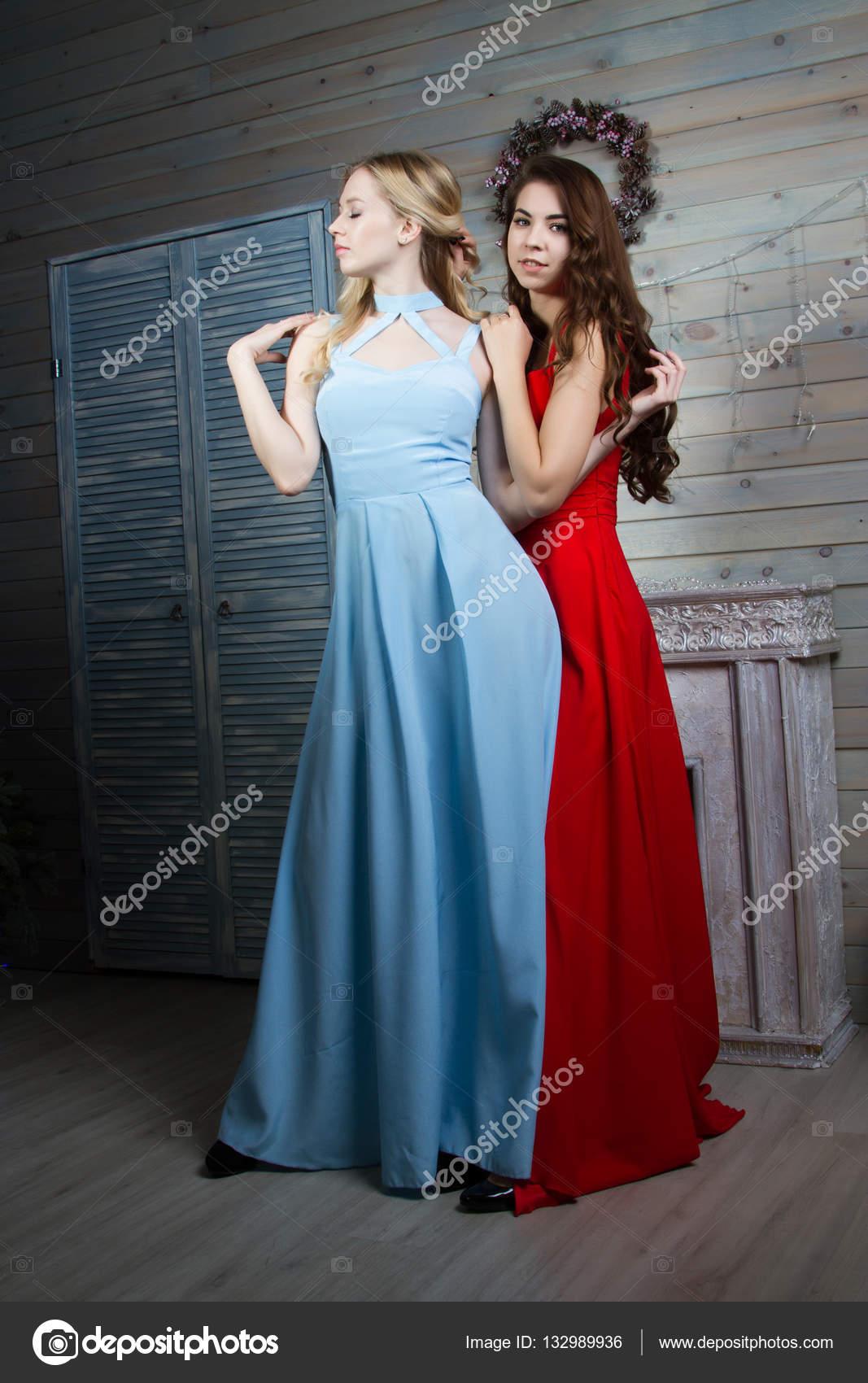 b138578e81f0 Due giovani ragazze in abiti lunghi in una stanza con un camino– immagine  stock
