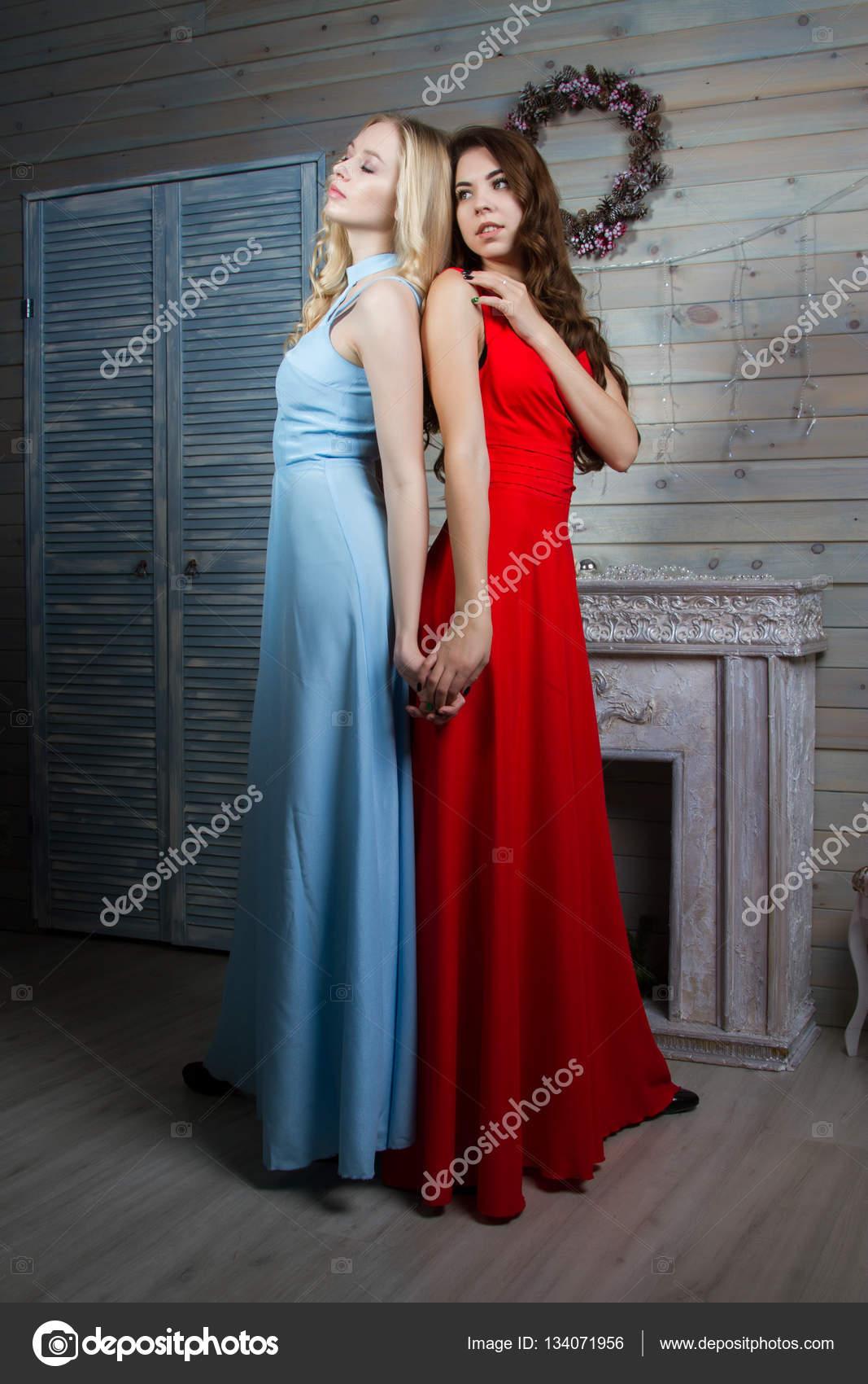 d4c2c677c124 Due ragazze in abiti da sera nella sala con camino — Foto Stock ...