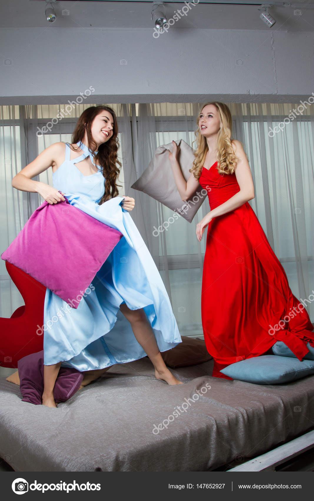263235fc1cfb Due ragazze in vestiti da sera su un letto in camera da letto– immagine  stock