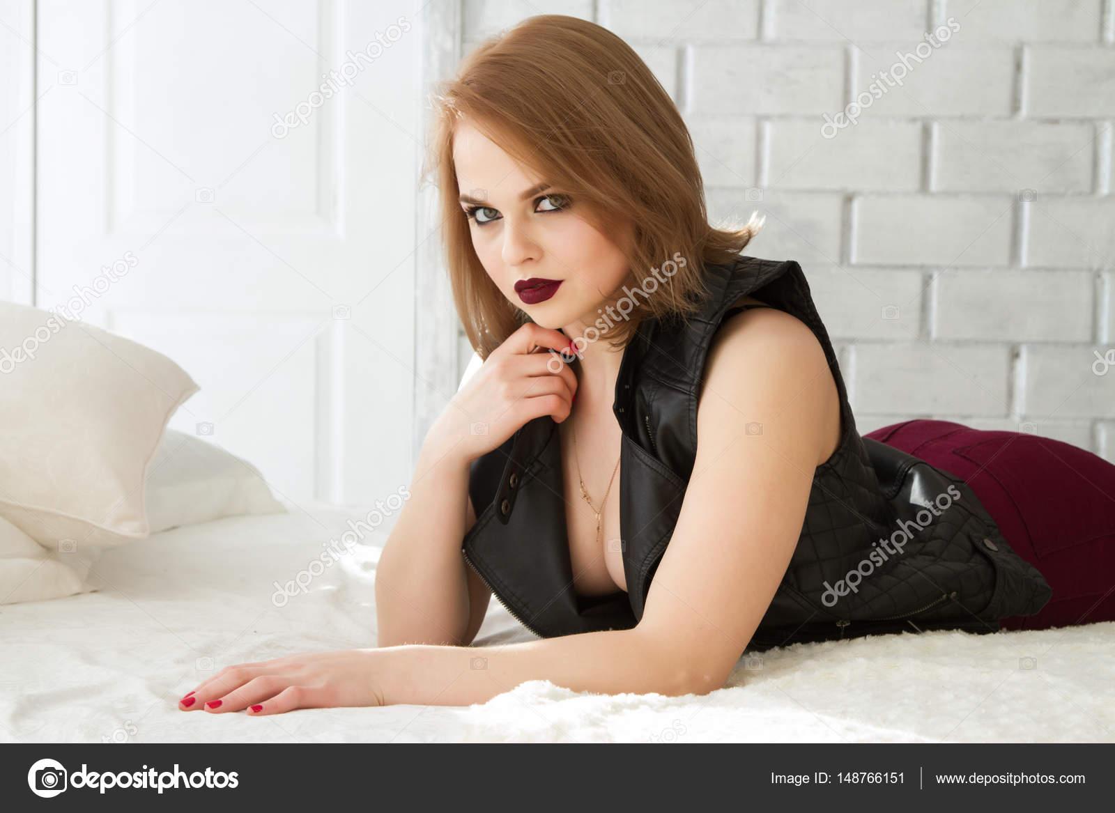 Jong meisje in een lederen jas ligt op een bed in de slaapkamer