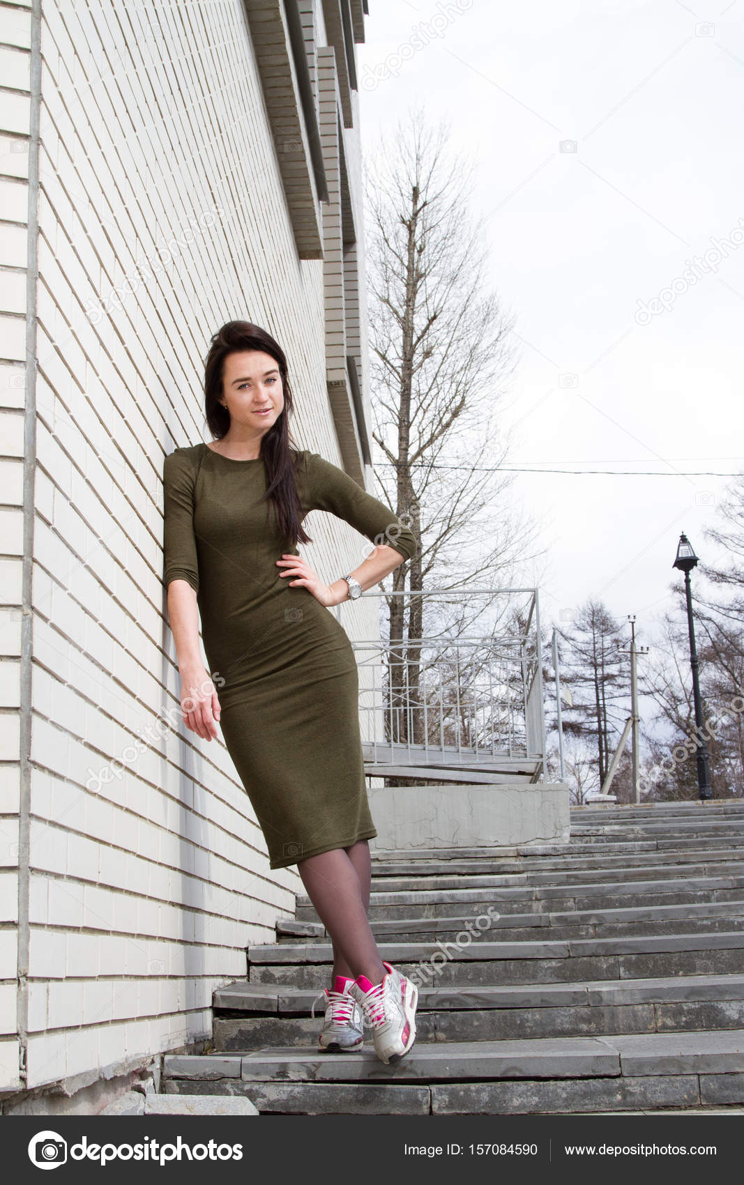 d9ddad481dbe Ragazza in un vestito e scarpe da ginnastica si leva in piedi vicino a un  muro di mattoni– immagine stock