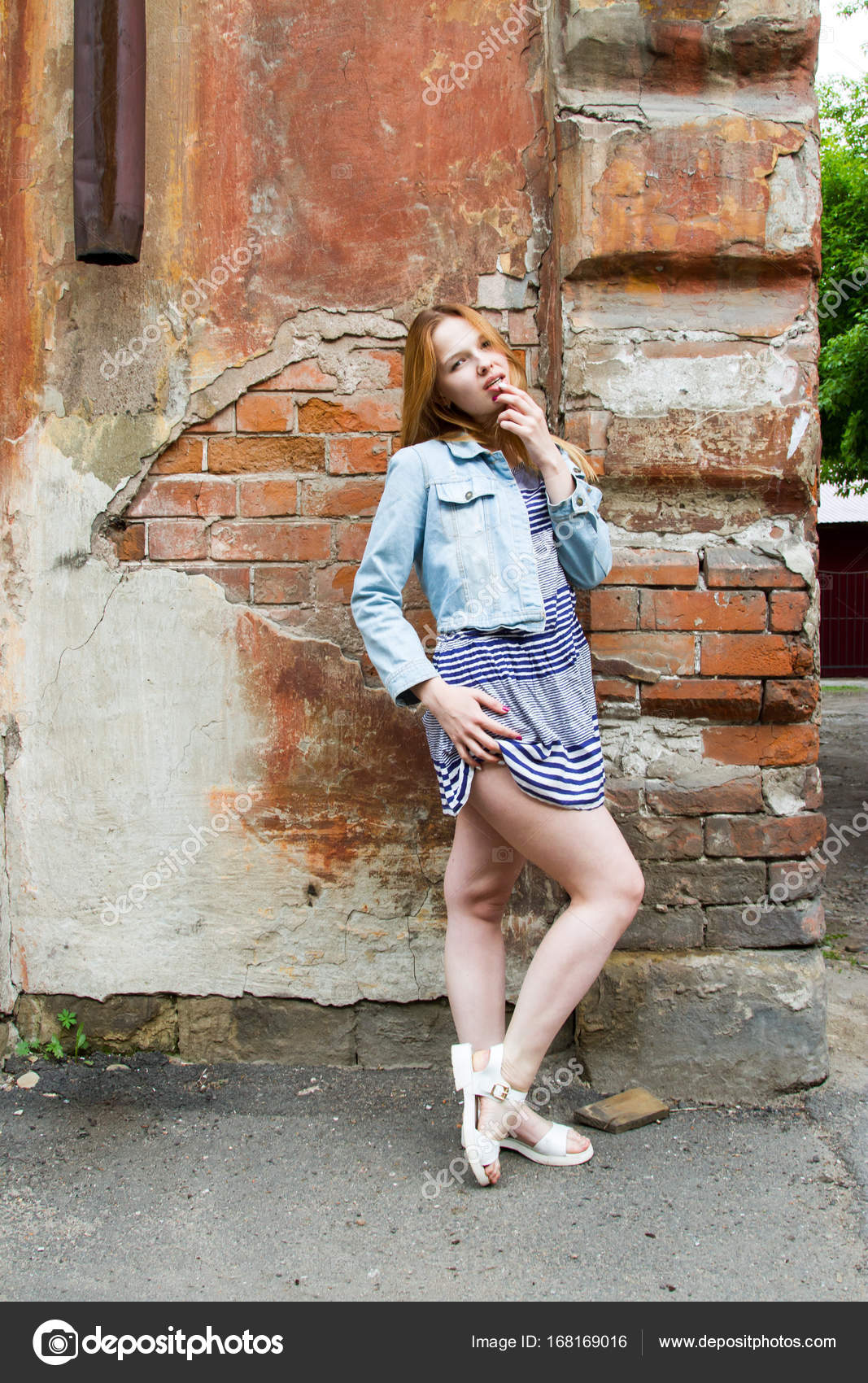 76362bc2a8 Chica en una falda corta está de pie por el muro de una casa antigua - ninas  con faldas cortas — Foto de ...