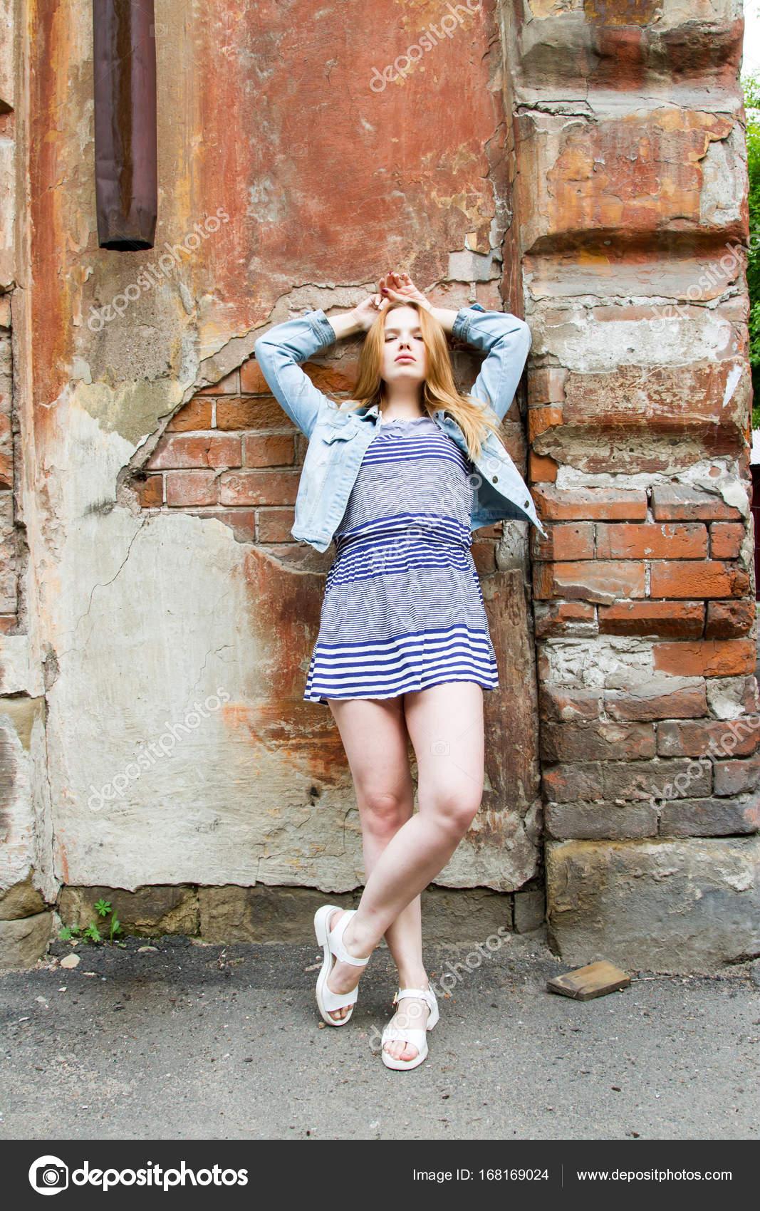 d'une mur en briques debout courte jupe de fille du près vieille est CxBoerd