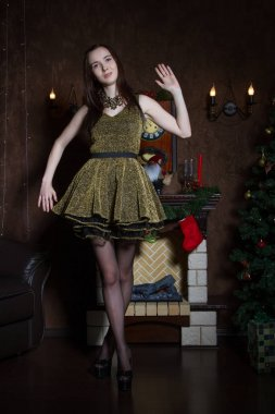 Girl in short dress on the background of a fireplace with gifts
