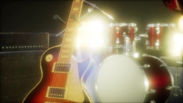Dobfelszerelés és gitár visszafogott színpadi világításban.