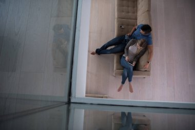 youg couple in living room with tablet top view