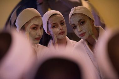 women putting face masks in the bathroom