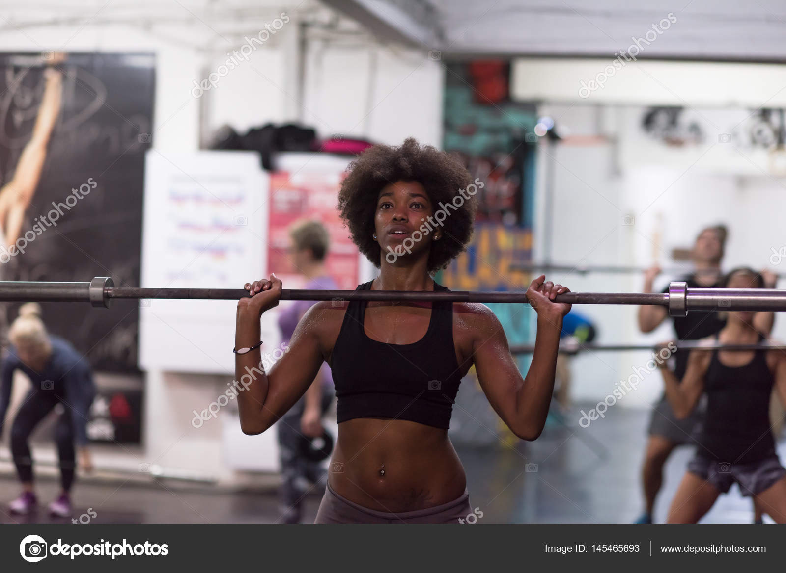 5585776a551ce Young Cute african american sport woman in fitness room lifting empty bar —  Photo by . ...