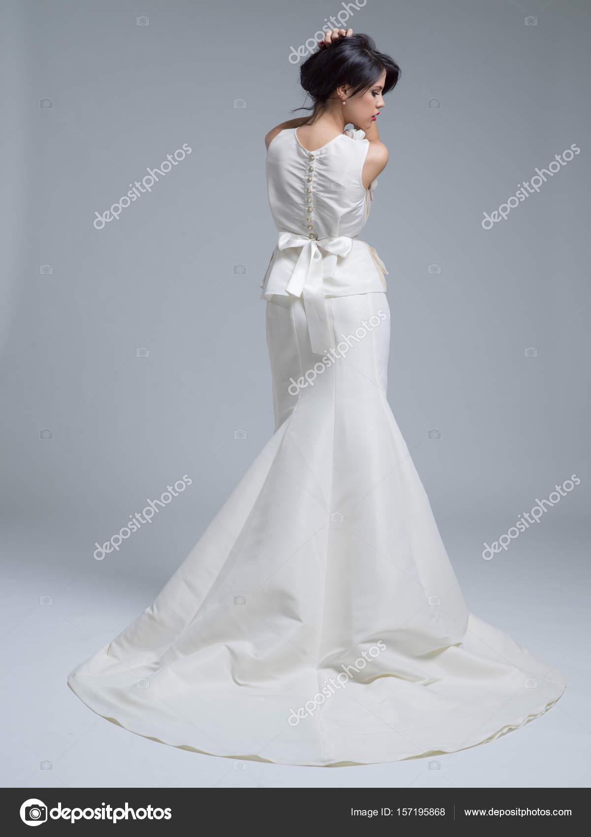 Vista posterior de una mujer joven hermosa en un vestido de novia ...