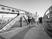 Urban sport, sano giovane coppia attraverso il ponte in città a fare jogging a mattina piena di sole