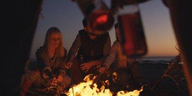 Gün batımında şenlik ateşi etrafında sahilde eğlenen bir grup genç.