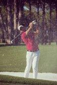 Golfové hráče, kteří odpálí záběr na kurz na krásný slunečný den