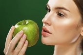 Head shot of woman holding green apple against green background