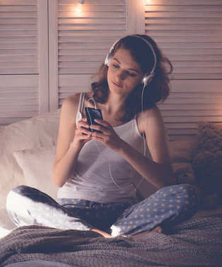 Young  woman relaxing in her bed, she is listening to music