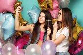 Zwei Freundinnen mit bunten Luftballons machen Selfie auf einem Foto