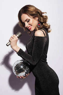 lifestyle and people concept: woman wearing black dress, holding disco ball and singing into microphone